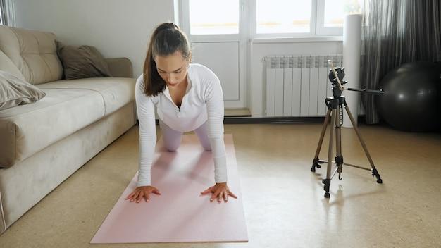Aantrekkelijke jonge vrouwelijke trainer in witte sportkleding drukt op de knieën en schiet videobegeleiding met mobiele telefoon in lichte kamer