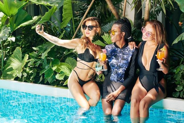 Aantrekkelijke jonge vrouwen in bikini die op de rand van het zwembad zitten en selfie nemen met haar mooie vrienden