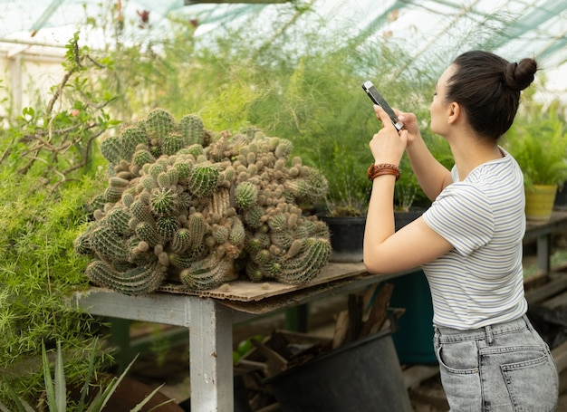 Aantrekkelijke jonge vrouwen tuinman in casual outfit doen foto van grote cactus op telefoon voor blog.