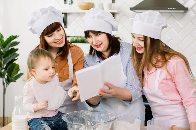 Aantrekkelijke jonge vrouwen, vrouw van middelbare leeftijd en kleine schattige dochter koken op keuken. samen plezier maken tijdens het maken van taarten en koekjes. vrouwen lezen het kookboek met recepten