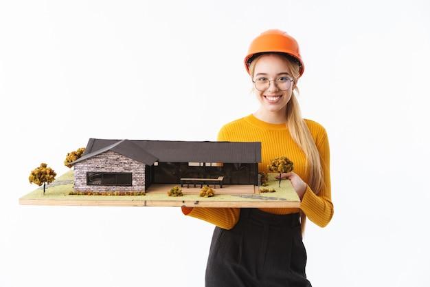Aantrekkelijke jonge vrouwenarchitect die bouwvakker draagt die zich over witte muur bevindt, die huismodel toont