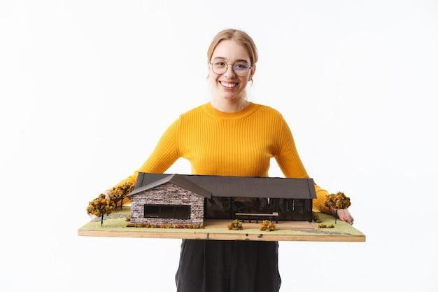 Aantrekkelijke jonge vrouwenarchitect die zich geïsoleerd over witte muur bevindt, die huismodel toont