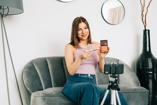 Aantrekkelijke jonge vrouwenvideoblogger die schoonheidsproducten via haar blog op sociale media toont