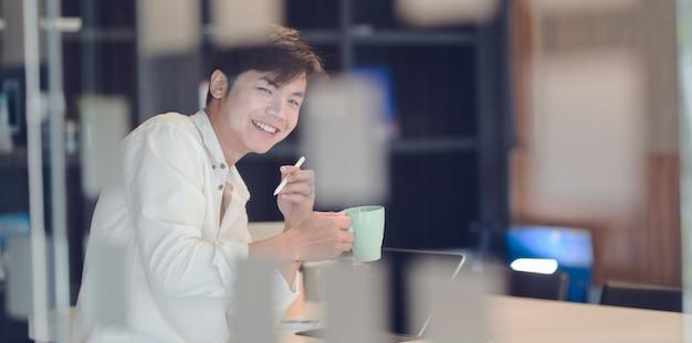 Aantrekkelijke jonge zakenman die een koffiepauze heeft