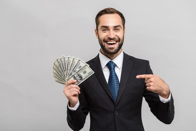 Aantrekkelijke jonge zakenman die een pak draagt dat geïsoleerd over een grijze muur staat, geldbankbiljetten toont, met de vinger wijst