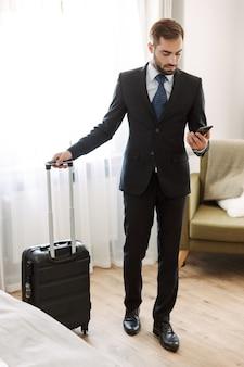 Aantrekkelijke jonge zakenman die een pak draagt dat in de hotelkamer staat en mobiele telefoon gebruikt terwijl hij een koffer draagt