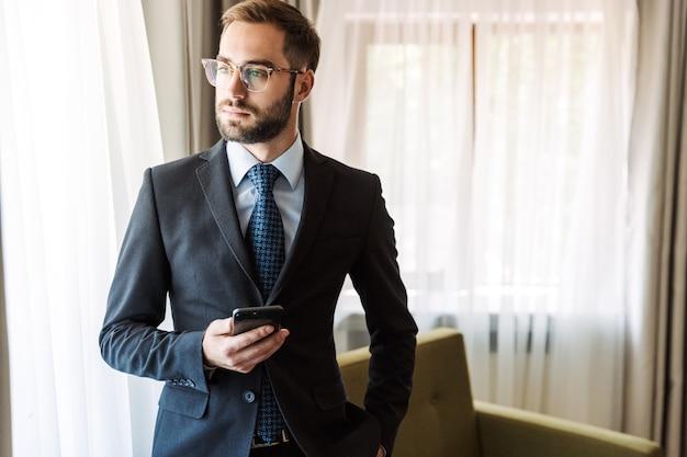 Aantrekkelijke jonge zakenman die een pak draagt dat in de hotelkamer staat en mobiele telefoon gebruikt