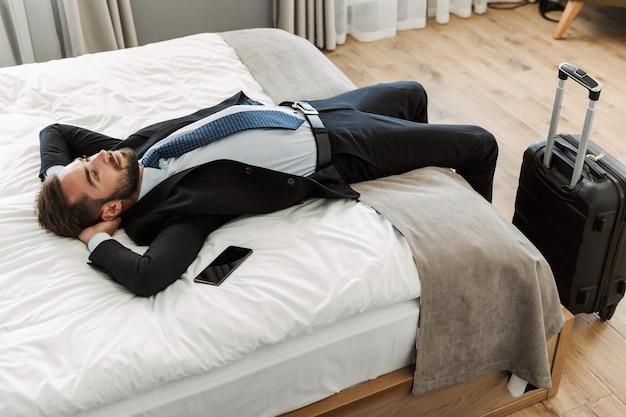Aantrekkelijke jonge zakenman die een pak draagt dat op een hotelbed ligt met een mobiele telefoon met een leeg scherm, net aangekomen