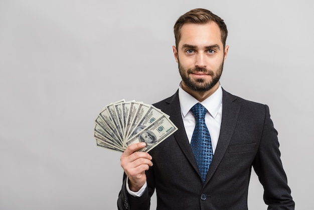 Aantrekkelijke jonge zakenman die een pak draagt dat over een grijze muur staat en geldbankbiljetten toont