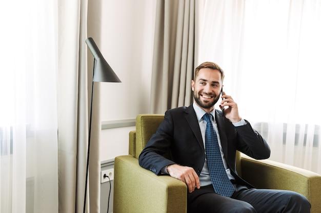 Aantrekkelijke jonge zakenman die een pak draagt, zittend in een stoel in de hotelkamer
