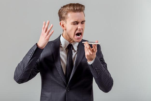 Aantrekkelijke jonge zakenman die op de telefoon spreekt.