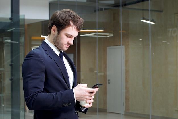 Aantrekkelijke jonge zakenman gebruikt smartphone in interieur van moderne kantoorgebouw
