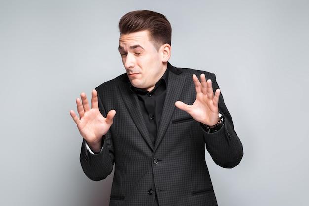 Aantrekkelijke jonge zakenman in zwarte jas, dure horloge en zwart shirt