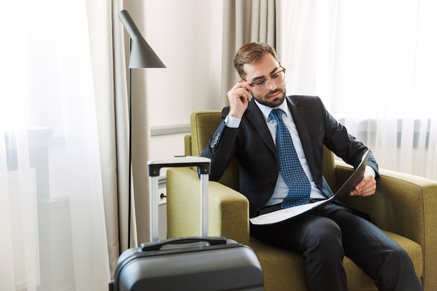 Aantrekkelijke jonge zakenman met een pak zittend in een stoel in de hotelkamer, werkend met documenten