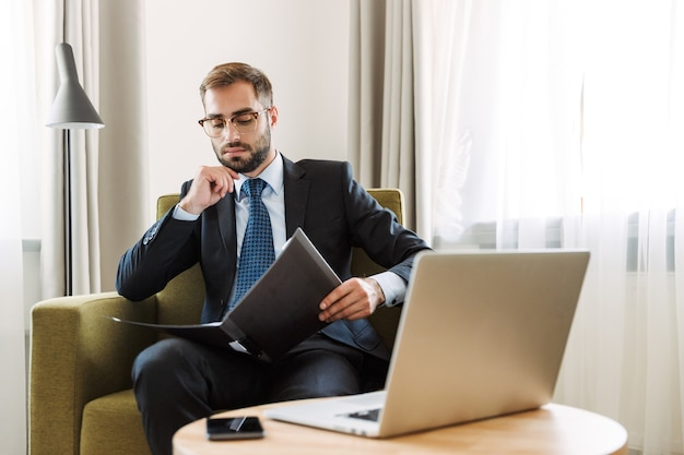 Aantrekkelijke jonge zakenman met een pak zittend in een stoel in de hotelkamer, werkend op een laptopcomputer, documenten vasthoudend