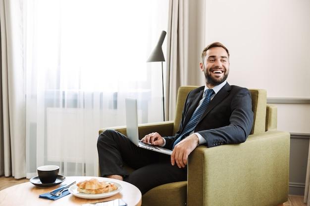 Aantrekkelijke jonge zakenman met een pak zittend in een stoel in de hotelkamer, werkend op een laptopcomputer tijdens het ontbijt
