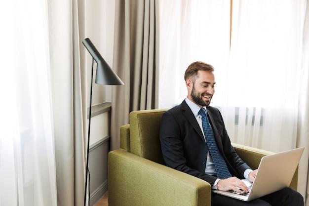Aantrekkelijke jonge zakenman met een pak zittend in een stoel in de hotelkamer, werkend op een laptopcomputer