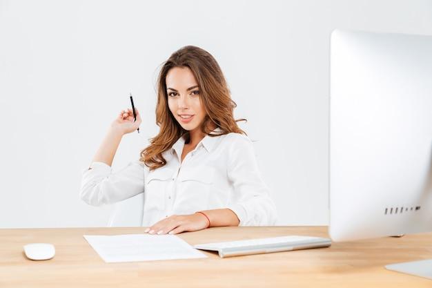 Aantrekkelijke jonge zakenvrouw die een pen vasthoudt terwijl ze aan het bureau zit met een laptop