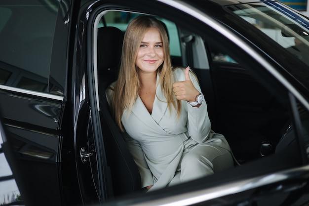 Aantrekkelijke jonge zakenvrouw die in de auto zit in de autoshowroom vrouw die een nieuwe auto kiest, mooi blond