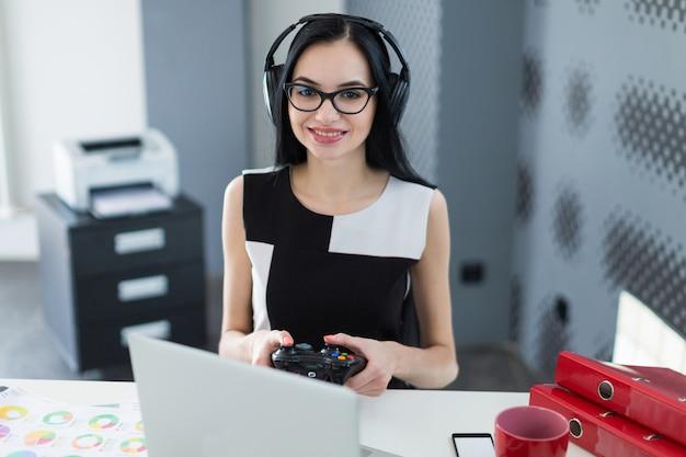 Aantrekkelijke jonge zakenvrouw in zwarte jurk, koptelefoon en bril zitten aan de tafel en spelen op laptop