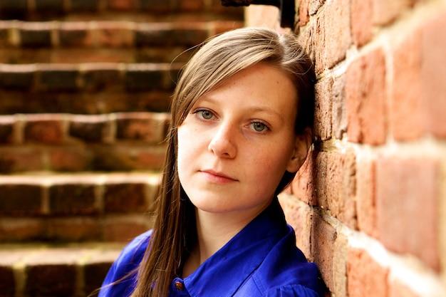 Aantrekkelijke jonge zelfverzekerde vrouw in een blauw shirt, leunend op een bakstenen muur en poseren