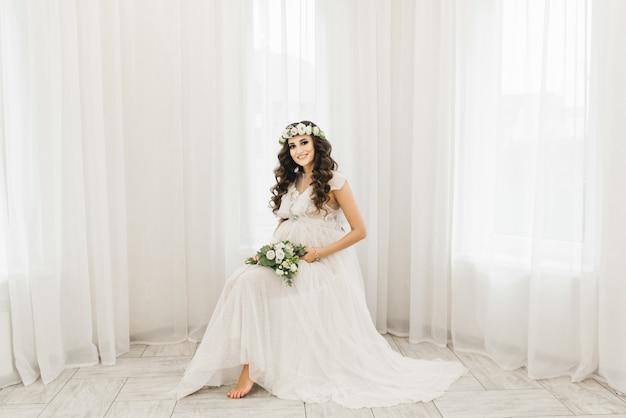 Aantrekkelijke jonge zwangere meisje in een witte jurk met krullen, een krans en een boeket bloemen. fotosessie wachten op de baby
