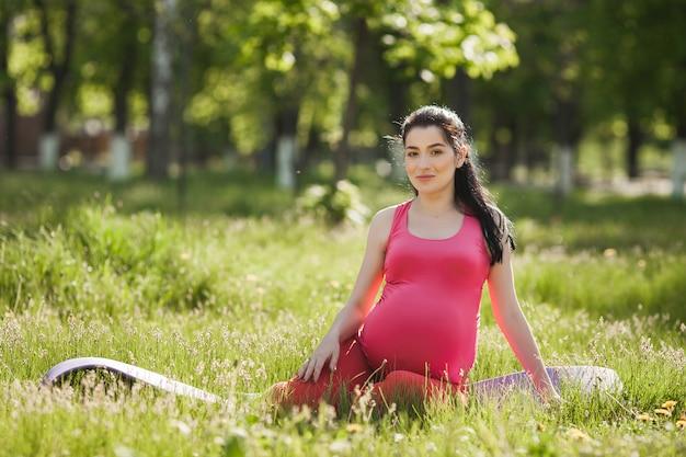Aantrekkelijke jonge zwangere vrouw die yogaoefeningen in openlucht in het park doet. verwacht dat een vrouw een gezonde en actieve levensstijl heeft.