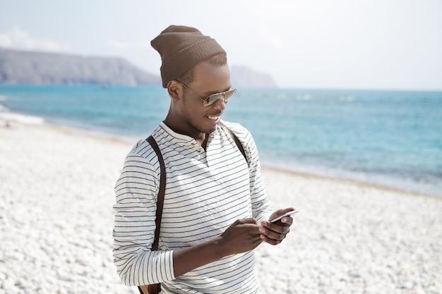 Aantrekkelijke jonge zwarte glimlachende mannelijke reiziger in trendy tinten met behulp van smartphone, het verzenden van e-mail naar zijn familieleden, op zoek gelukkig tijdens het wandelen door de oceaan alleen. mensen, levensstijl en reizen