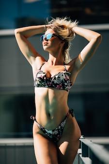 Aantrekkelijke jongelui en vrouw in zwarte bikini bij het zwembad.