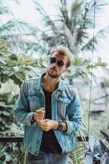 Aantrekkelijke jongeman die zich voordeed op een tropische locatie, op een achtergrond van palmbomen en groen