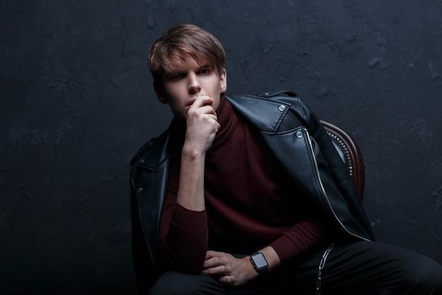 Aantrekkelijke jongeman in een stijlvolle zwarte leren jas in rode golf in zwarte jeans in trendy schoenen met stijlvolle horloges poseren in een donkere studio in de buurt van een zwarte muur. knappe stijlvolle moderne kerel