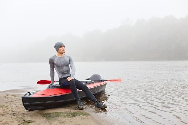 Aantrekkelijke jongeman in grijze pet en shirt, die zich voordeed op de oever van de rivier, dromerig op zoek in de verte