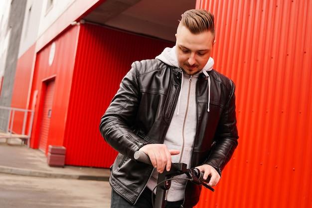 Aantrekkelijke jongeman op elektrische scooter op rode achtergrond