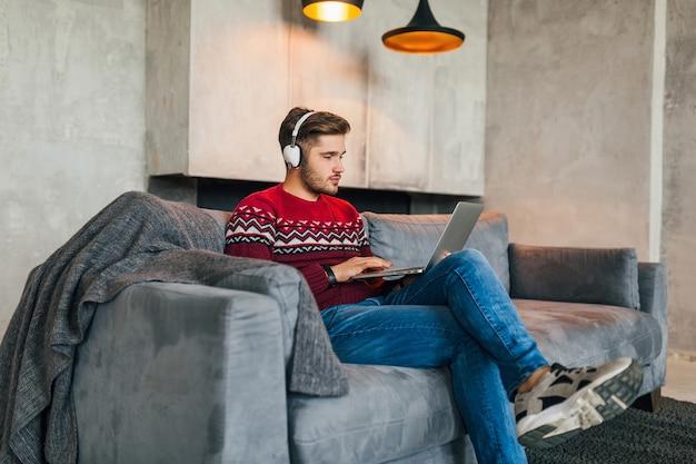 Aantrekkelijke jongeman op sofa thuis in de winter in koptelefoon, luisteren naar muziek, dragen rode gebreide trui, bezig met laptop, freelancer, serieus, druk, typen, geconcentreerd