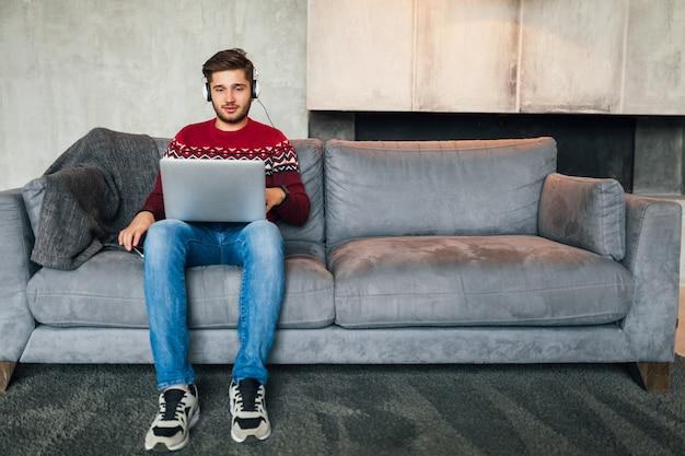 Aantrekkelijke jongeman op sofa thuis in de winter in koptelefoon, luisteren naar muziek, dragen rode gebreide trui, bezig met laptop, freelancer