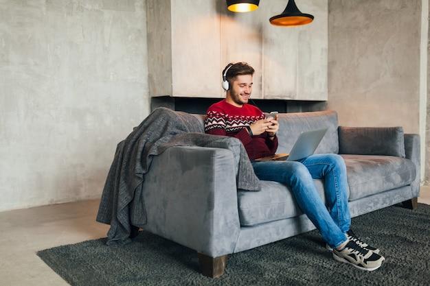 Aantrekkelijke jongeman op sofa thuis in de winter met smartphone in koptelefoon, luisteren naar muziek, dragen rode gebreide trui, bezig met laptop, freelancer, glimlachen, gelukkig, positief