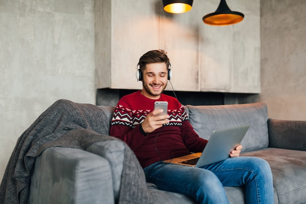 Aantrekkelijke jongeman op sofa thuis in de winter met smartphone in koptelefoon, luisteren naar muziek, dragen rode gebreide trui, bezig met laptop, freelancer