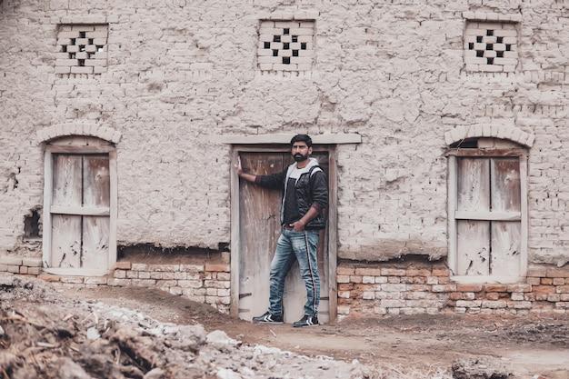 Aantrekkelijke jongen die voor het oude huis staat, buiten schieten in het dorp,