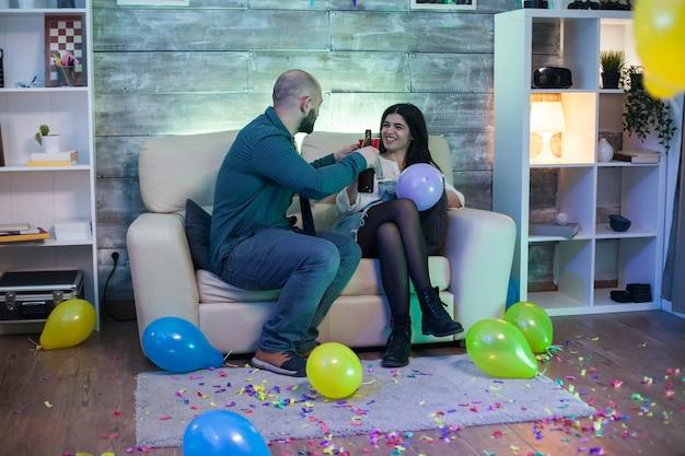 Aantrekkelijke kale man en mooie vrouw met een gesprek zittend op de bank op een feestje. een drankje nemen.