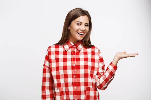 Aantrekkelijke kastanje vrouw in rood en wit overhemd ziet er recht uit