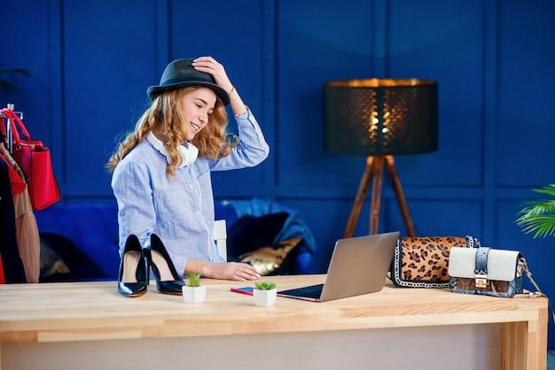 Aantrekkelijke kaukasische blogger die een hoed past tijdens het opnemen van video.