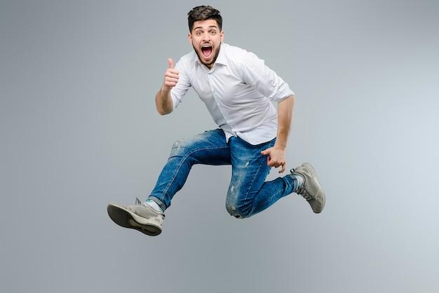 Aantrekkelijke kerel in wit overhemd die en duimen springen tonen die omhoog over grijze achtergrond worden geïsoleerd