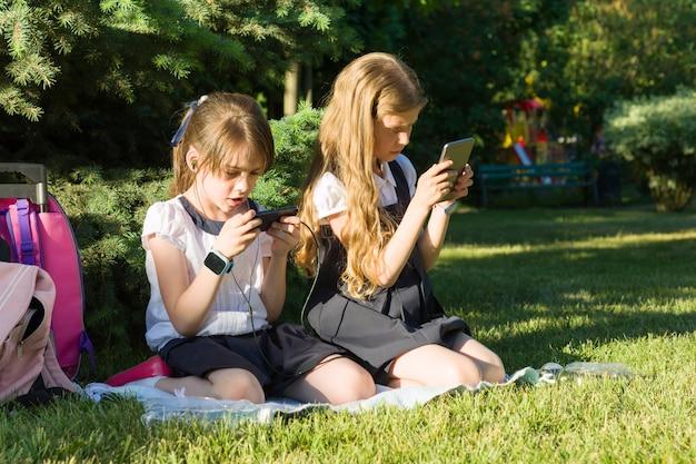 Aantrekkelijke kleine vriendinnen schoolmeisjes met rugzakken, telefoons