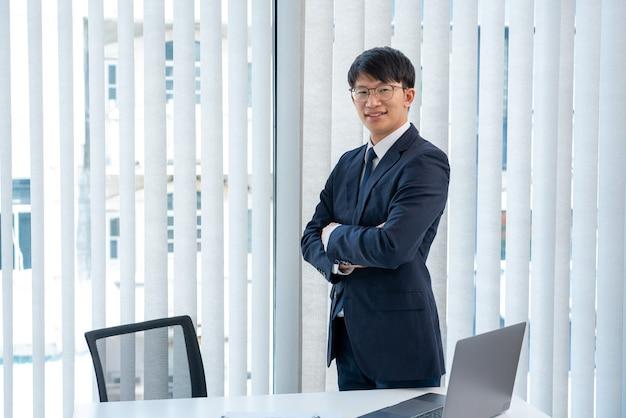 Aantrekkelijke knappe aziatische zakenlieden die in glazen positief gelukkig glimlachen