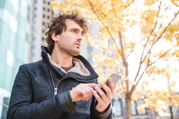 Aantrekkelijke knappe, bedachtzame, gekrulde man die een mobiele telefoon vasthoudt en in de herfst in de straat van de stad wacht