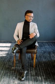 Aantrekkelijke knappe gelukkig lachend afro-amerikaanse zakenman draagt een lichte jas en bril zittend op een leren stoel op een donkere achtergrond