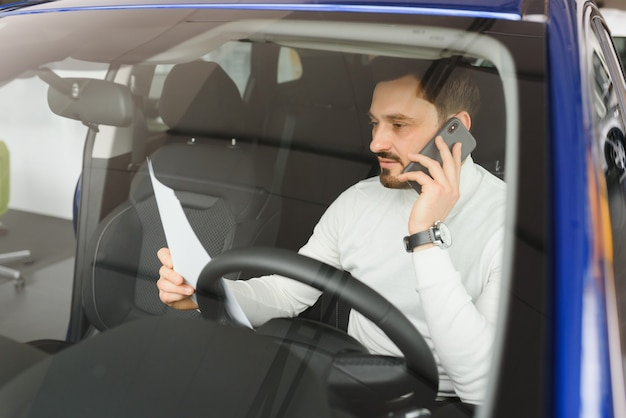 Aantrekkelijke knappe jonge zakenman met behulp van mobiele slimme telefoon in de auto.