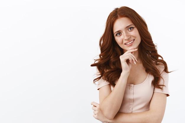 Aantrekkelijke kokette roodharige vrouw in blouse raakt kin bedachtzaam aan, glimlachend enthousiast kijkende nieuwsgierige camera, denkend, nadenkend over een beslissing