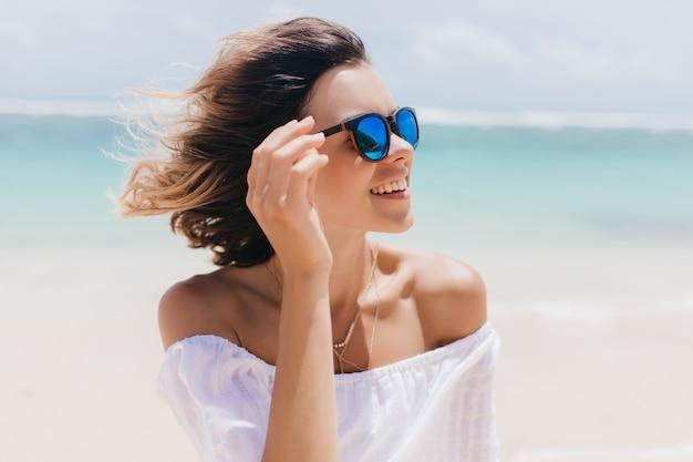 Aantrekkelijke kortharige europese vrouw koelen in het resort. geweldige gelooide vrouw in zonnebril ontspannen aan zandstrand in de zomer.