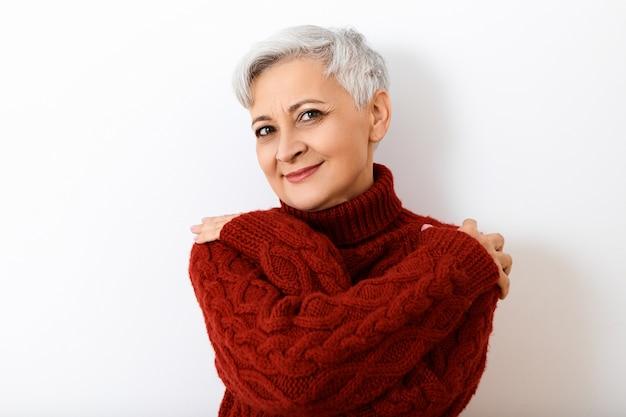 Aantrekkelijke kortharige senior volwassen vrouw met birhgt make-up poseren geïsoleerd dragen van stijlvolle gebreide trui, zichzelf knuffelen, met vrolijke vrolijke gezichtsuitdrukking